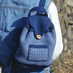 "Students and other folks on the go will love our mini backpack! Lined with coordinating fabric, the tote features a tasseled drawstring and a top flap that latches shut with a large wooden button. Two pockets, one on the inside and one on the outside, add more room to tuck away take-along necessities. It is crocheted using worsted weight yarn and sizes B (2.25 mm) and C (2.75 mm) hooks. Number of Designs: 1 Backpack Approximate Design Size: 11"" x 10""<br /> <br /><div style=""width: 300px…"