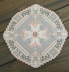 This lovely, handmade hardanger doily is stitched on a blue-gray fabric with white and pink threads.  It features so many delicate details and measures approx. 11.5x11.5