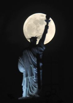 The full moon rises behind Statue of Liberty replica atop of a hotel in Kosovo's capital Pristina on Saturday, May 5, 2012