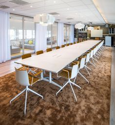 modern large meeting room with soft brown carpet and modern office furniture also unique hanging light fixture add glass room divider with white curtain: fun and playful colors at modern office in stockholm