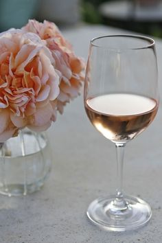 A glass of blush wine in the light of dusk
