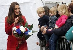 Hello there! The Duchess of Cambridge waves to three small children as she greets the crowds at Fonteviot fete who handed her a patriotic bouquet