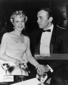 1965: Married American actors Barbara Eden and Michael Ansara holding hands while seated at a table with cocktails in formal attire.