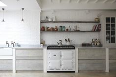 neutral scandinavian modern kitchen, lime-washed parquet floor, butler sink, carrara marble counters, and a white aga