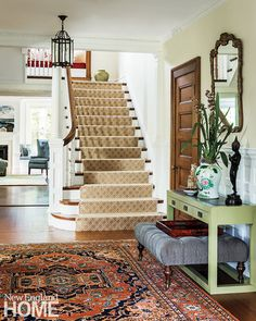 In the foyer, the marriage of an antique mirror and a modern console sets the tone for the home's striking old-meets-new decor. An antique oriental rug and a contemporary stair runner from Stark also make pleasing partners.