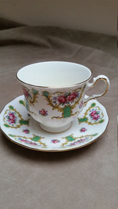 Bright bone china teacup and saucer set, made in England by Queen Anne, (Shore and Coggins Ltd), between 1959 and 1966. This is pattern number 8513, featuring magenta rose groupings and blue flowers, bracketed by green and gold decorative elements, on a white ground. The bottoms of the