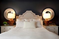 I LOVE the two circular mirrors layered against the lamps and lack of a focal piece above the headboard.