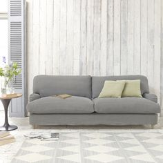 Loaf's timeless British sofa in light grey linen and weathered oak legs