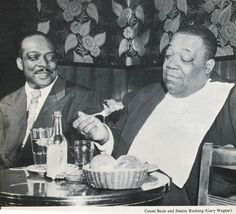 """Count Basie looks on in amazement as his vocalist, blues shouter """"Little"""" Jimmy Rushing (Oklahoma City), wolfs it down."""