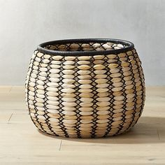 Free Shipping.  Shop Ace Natural Basket.   Twisted banana leaf shapes up nicely to create this graphic basket with black jute Xs up the sides.  Topped with a rim of black leather, this catchall is storage you'll want to keep on display.