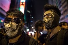 Umbrella Revolution Hong Kong, Masked protesters stand at the barriers dividing the police from the crowds in Mongkok October 25, 2014 in Hong Kong, Hong Kong. While the main protest site remains peaceful Mongkok is still a potential flash point. Sunday will start a two-day referendum to gauge protesters response to government proposals to end the street occupation that has been going on a month. (Photo by Paula Bronstein/Getty Images)