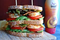 A monster club sandwich with chile lime shrimp, crispy bacon, tons of avocado, lettuce, tomato, and a honey mustard hummus spread.