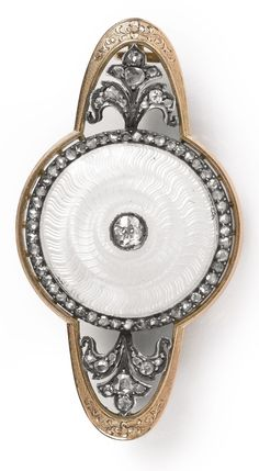 A FABERGÉ DIAMOND-SET GOLD AND GUILLOCHÉ ENAMEL BROOCH, WORKMASTER AUGUST HOLLMING, ST. PETERSBURG, 1898-1908 a circular disk enameled in transparent white over a wavy engine-turned ground centered with a diamond and framed by a band of rose diamonds with diamond-set floral sprigs on each side, struck with workmaster's initials.