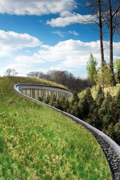Structure blends into landscape rising from the terrain with curved and natural lines.
