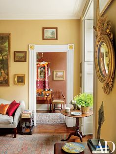 A gilt-wood mirror hangs in the room, near a circa-1760 Chippendale tilt-top table.