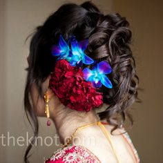 curly updo with a floral hairpin made of blue orchids and red carnations.