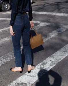 Tanned mules with a black tip, a variation of the two toned slingbacks from Chanel. A high waisted dark jeans the sculpts the body and a navy blue silk shirt tucked in. Each element of the outfit is chic and well adapted.