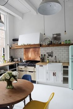 "This kitchen from Brick Studio in Amsterdam has a lot of different materials and time periods happening. White cabinets, old-school copper backsplash, beige oven, mint green Smeg fridge, and modern shell chairs give it a haphazard feel that stylish & unapologetic people pull off on a regular basis. But all combined, the high quality materials and earthy quality make you feel like anything more ""matchy-matchy"" would be in bad taste."