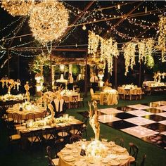 More luxurious event with golden lights hung across the room and a large checkerboard dance floor in the centre.