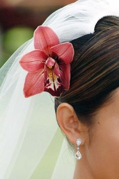 A matching red orchid adorns the bride's hair, tucked behind her tulle veil.