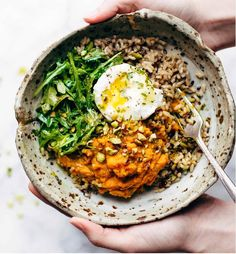 Brown rice and red quinoa, turmeric mashed sweet potatoes, poached egg, greens, pistachios, and zippy lemon herb dressing; courtesy of Pinch of Yum