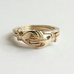 Gimmel rings are rings from antiquity that feature several links or loops that fit together to form one ring.  This handmade, triplet fede gimmel ring has been hand carved and inspired by these promise rings of the 1600s, and features two clasped hands that have beautifully detailed