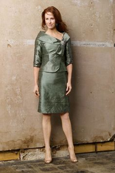 Meadow timeless dupioni silk 2-piece suit, asymmetrical jacket with wrap collar, classic crystal brooch, 3/4 length sleeves and above knee length skirt.