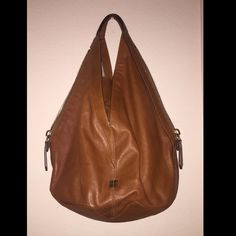 Authentic GIVENCHY hangbag/purse. Authentic GIVENCHY handbag/purse. Brown hobo style with calfskin leather and V-shaped shoulder strap. Has side zippers. Inside looks brand new! Givenchy Bags Hobos