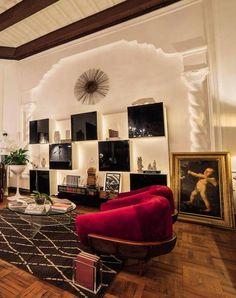 Hall de entrada e biblioteca - Orlando Espinoza Silva. Eclético, o espaço integra o design de diferentes épocas em harmonia. Algumas peças são do século 19 e remetem ao estilo colonial, mas há lugar para o mobiliário das charmosas décadas de 1950 e 1960, além de peças de arte contemporânea.