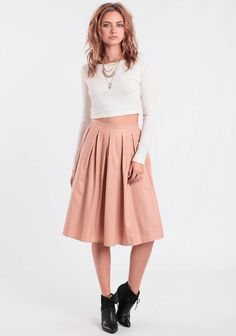 Light pink midi skirt rendered in faux leather and designed with box pleats all around for added flare. Complete with a hidden side zipper closure. We love it paired with a black crop top and str...