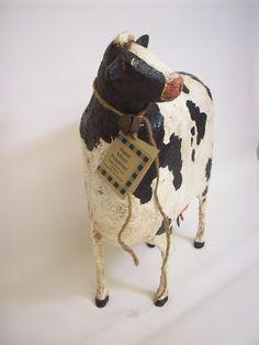 Este banco de vaca fresca 13 pulgadas de alto, 10 pulgadas de largo y unos 4 1/2 pulgadas profundidad. Está hecha de muchas capas de papier maché/aserrín mezcla esculpido sobre 2 bandejas de espuma de poliestireno y un alambre muy resistente. Ha sido pintado, barnizado y sellado.    Lleva un lazo de yute simple y oxidada campana alrededor de su cuello.    Tiene una abertura en la parte superior de la espalda por monedas. Su ubre está formado por un corcho extraíble grande para cuando…