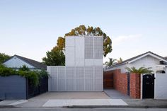 Fibre cement sheet facade flushed with operable perforated metal shutters/garage door - May Grove Residence by Jackson Clements Burrows Architects Melbourne