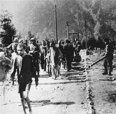 American soldiers walk among emaciated survivors along a road in the Ebensee concentration camp.   Date: May 8, 1945   Locale: Ebensee, Austria   Credit: USHMM, courtesy of Bert Weston