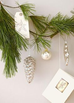 Branch out!  Hang Christmas cards, embellished tags and ornaments from a single evergreen branch tacked to the wall. More ideas for using natural decor in Christmas decorating: http://www.midwestliving.com/homes/seasonal-decorating/nature-inspired-christmas-decorations/?page=11