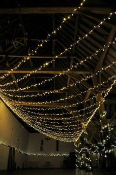The sweeping, stunning fan canopy of fairy lights in the barn at Ufton Court weddings