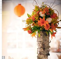 For an earthy touch to the decor, Charlie cut down sections of Aspen trunk from his family's ranch near Denver. Bright ranunculus, roses and freesia draped down the bark, while table numbers leaned up against it.  Love!!!!!!!