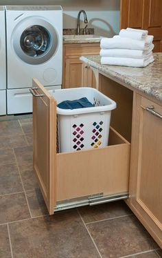 Custom rollout for laundry basket in mudroom/laundry room.  Crown Point Cabinetry Gallery #71