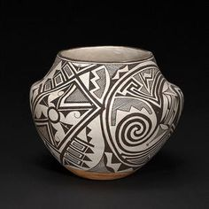 An Acoma jar - Marie Z. Chino, with a densely detailed pattern of circular medallions and feather-lined box devices.