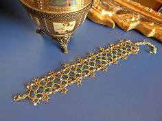 Braccialetto realizzato a chiacchierino con filato oro Gütermann, perle Rocailles e cristalli verdi Swarovski.