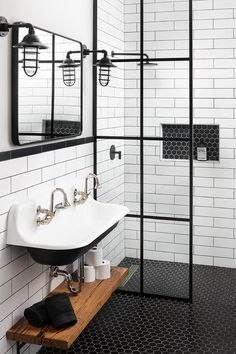 Kohler Brockway sink paired with an oil rubbed bronze mirror and wooden shelves underneath mounted on a white subway tiled wall.