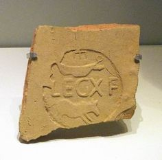 A fragment of an ancient Roman pottery roofing tile with the stamp of the Roman army's Tenth Legion, 'LEG X F', and its symbols, a wild boar and battleship. (The Israel Museum)