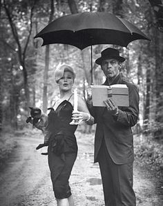 The actress Ginger Rogers with her fifth husband, actor William Marshall. Apparently spoofing the film Bell Book & Candle. Complete with Pyewacket cat. In the rain.