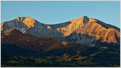 First Light On Mount Sopris... The first rays of morning light highlight Mount Sopris and its mantle of fall colors. In the Elk Range near Carbondale, Colorado.