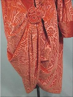 "c. 1919 Imported by I. MAGNIN & Co. Coral Embossed Cocoon Velvet Evening Wrap Coat, in a rich ""chinese coral"" color in a gorgeous embossed deco design velvet. Fully lined in matching plain velvet. Closure is a masterful twisted velvet design medallion. Collar can be worn up or down.(detail) (hva)"