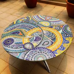 Discarded glass table transformed into blue and orange mosaic twirls