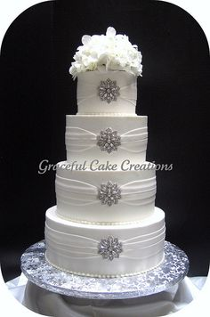 Elegant White Butter Cream Wedding Cake with White Sashing and Crystal Brooches