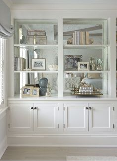 Mirror backed shelves - could be a great way to get light into that end of the room