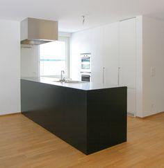 Küche mit Edelstahlabdeckung, schwarz und weiss lackierte Fronten.