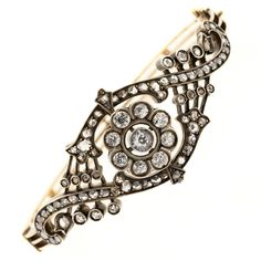 1870s Victorian Old Cut Diamond Silver Gold Clamper Bracelet. This pristine Victorian diamond, silver & gold bracelet is from the 1870s. The antique silver topped 14KT yellow gold belly design bracelet features a central diamond cluster of nine Old Mine Cut Diamonds, surrounded by swirl designs set with seventy two Old cut Diamonds. All diamonds are evaluated as H/J – SI/I1.