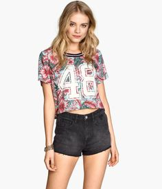 This cropped shirt pulls from designs of the 1990s. Cropped shirts were a very popular style. Her shirt is also mimicking a sports jersey in the style lines at the collar and the jersey numbers on the front. And while mixing active wear and ready to wear is popular now, it was also common in the 1980s. The 80s were home to a fitness revolution, it was extremely popular for women to do jazzercise and aerobics and wear the clothing appropriate for those activities (flash dance). Addy Forte 4/4